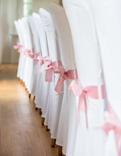 Hochzeitsdekorationen - festliche Stuhlhussen mit rosa Schleifen